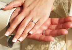 Mani degli sposi sposati con le fedi nuziali immagini stock