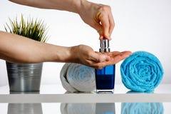 Mani degli uomini sull'erogatore del sapone nel bagno Fotografia Stock