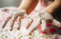 Mani dei bambini che giocano con una farina fotografia stock libera da diritti