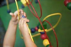 Mani dei bambini che giocano il bambino di legno di Maze Educational Game Toy del cavo Fotografia Stock Libera da Diritti