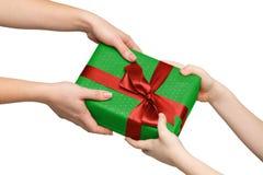 Mani dei bambini con il contenitore di regalo su bianco Immagini Stock