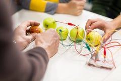 Mani dei bambini con il corredo di invenzione alla scuola di robotica immagine stock