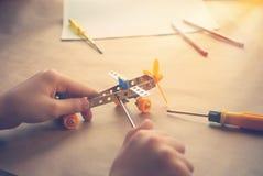 Mani dei bambini con l'aereo del ferro del giocattolo Costruttore del metallo con i cacciaviti Il sogno, gioca e crea immagini stock libere da diritti
