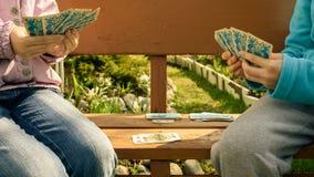 mani dei bambini e delle carte da gioco Fotografia Stock