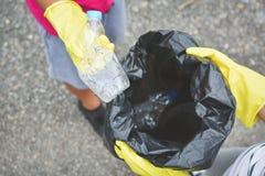 Mani dei bambini in guanti gialli che prendono vuoto della plastica della bottiglia nella borsa del recipiente Fotografia Stock