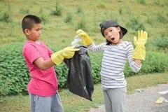 Mani dei bambini in guanti gialli che prendono vuoto della plastica della bottiglia nella borsa del recipiente Fotografie Stock
