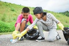 Mani dei bambini in guanti gialli che prendono vuoto della plastica della bottiglia nella borsa del recipiente Fotografia Stock Libera da Diritti