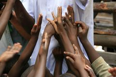 Mani dei bambini sollevate, elemosinando, l'Africa occidentale Fotografia Stock