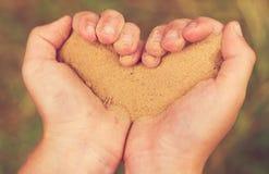 Mani dei bambini sotto forma di cuore con la sabbia Fotografie Stock