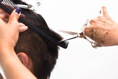 Mani dei capelli della guarnizione dello stilista di capelli con un pettine e le forbici Immagine Stock