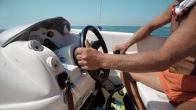 mani dei capitani che girano il volante alla barca a vela Fotografie Stock Libere da Diritti