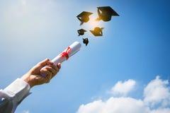 Mani dei laureati che gettano i cappelli di graduazione fotografia stock