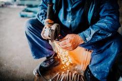 Mani dei lavoratori dell'industria che tagliano ferro con la smerigliatrice di angolo immagini stock libere da diritti