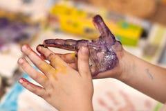 Mani dei piccoli bambini che fanno Fingerpainting Immagine Stock