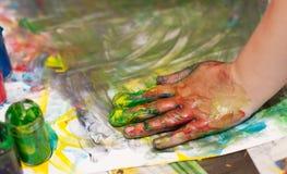 Mani dei piccoli bambini che fanno Fingerpainting Immagini Stock