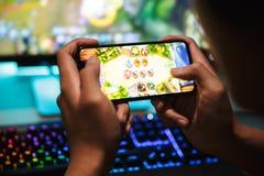 Mani dei video giochi di gioco del ragazzo 16-18 del gamer sullo smartphone e sulla c fotografia stock