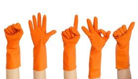 Mani dei volontari in guanti di gomma gialli che mettono sull'isolato su sul concetto volontario del fondo bianco immagine stock