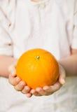 Mani del bambino che tengono arancio maturo Fotografia Stock Libera da Diritti