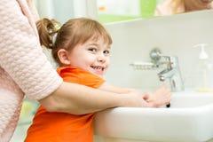 Mani del bambino di lavaggio della madre immagini stock libere da diritti