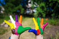 Mani del bambino dipinte nei colori luminosi isolati sul fondo della natura di estate immagini stock