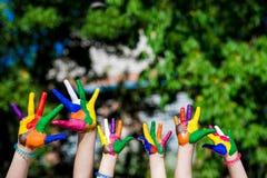 Mani del bambino dipinte nei colori luminosi isolati sul fondo della natura di estate Fotografia Stock