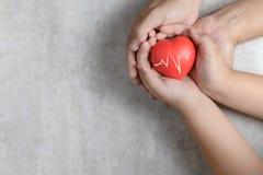 Mani del bambino e del padre che tengono cuore rosso su marmo fotografie stock libere da diritti