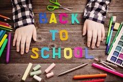 Mani del bambino sulla tavola con i rifornimenti di scuola fotografia stock