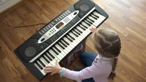 Mani del bambino sulla vista superiore della tastiera di piano video d archivio