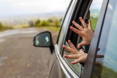 Mani del bambino in una finestra di automobile durante il viaggio alla vacanza immagini stock libere da diritti