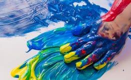 Mani del bambino verniciate in vernici variopinte Concetto di istruzione, della scuola, di creatività e della pittura fotografia stock libera da diritti