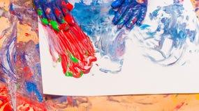 Mani del bambino verniciate in vernici variopinte Concetto di istruzione, della scuola, di creatività e della pittura fotografia stock