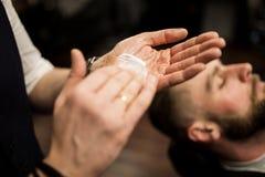 Mani del barbiere che sfregano radendo schiuma Fotografia Stock