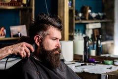 Mani del barbiere con il tagliatore ed il pettine, fine su Cliente barbuto dei pantaloni a vita bassa che ottiene acconciatura Co immagini stock libere da diritti