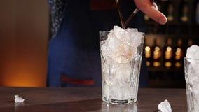 Mani del barista che versano simultaneamente due ingredienti del cocktail sui cubetti di ghiaccio video d archivio