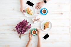 Mani del caffè delle coppie e dei croissant beventi di cibo sulla tavola immagini stock libere da diritti