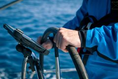 Mani del capitano al controllo del timone della barca a vela Fotografia Stock Libera da Diritti