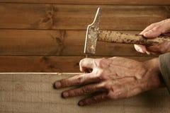 Mani del carpentiere con il legno ed il chiodo del martello Fotografie Stock