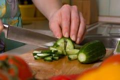 Mani del cetriolo di taglio del cuoco. Immagine Stock