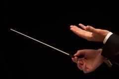 Mani del conduttore di concerto con il bastone fotografie stock