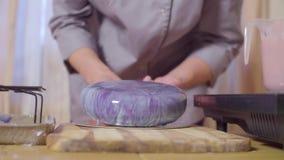 Mani del confettiere che mette dolce con la glassa dello specchio sul supporto del dolce archivi video