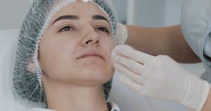 Mani del cosmetologo s che preparano paziente per le labbra di correzione e di contorno Disinfezione del fronte La procedura di archivi video