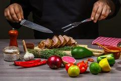 Mani del cuoco unico che cucinano la bistecca, le verdure e le spezie della carne con dalle mani del cuoco unico su fondo di legn immagini stock
