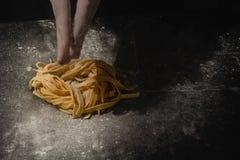 Mani del cuoco unico che fanno gli spaghetti, pasta, tagliatelle con pasta fresca sulla tavola nera con immagini stock libere da diritti