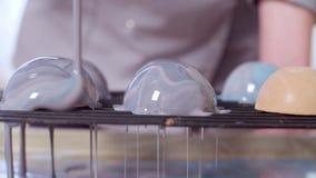 Mani del cuoco unico di pasticceria che versa la glassa calda dello specchio sulle palle di mousse congelata stock footage