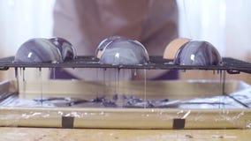 Mani del cuoco unico di pasticceria che versa la glassa calda dello specchio sulle palle di mousse congelata archivi video