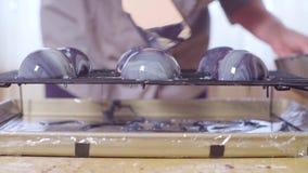 Mani del cuoco unico di pasticceria che versa la glassa calda dello specchio sulle palle di mousse congelata video d archivio