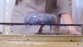 Mani del cuoco unico di pasticceria che versa la glassa multicolore dello specchio su un grande dolce archivi video