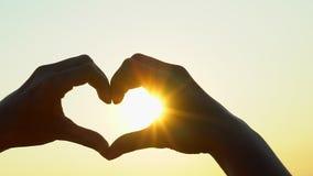 Mani del cuore di tramonto La donna modella il cuore con consegna il sole sull'alba o sul tramonto di estate della natura E video d archivio