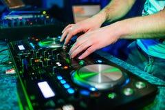 Mani del DJ ad un miscelatore per musica mescolantesi in un'atmosfera del night-club Fotografia Stock