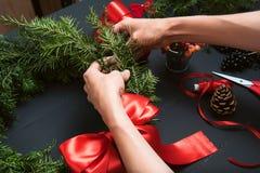 Mani del fiorista che fanno la corona di Natale Immagini Stock Libere da Diritti